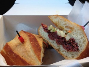 Braised Corned Beef Cheek, Sriracha Honey Mustard, Napa Slaw, Apple Horseradish Catsup on a Baguette