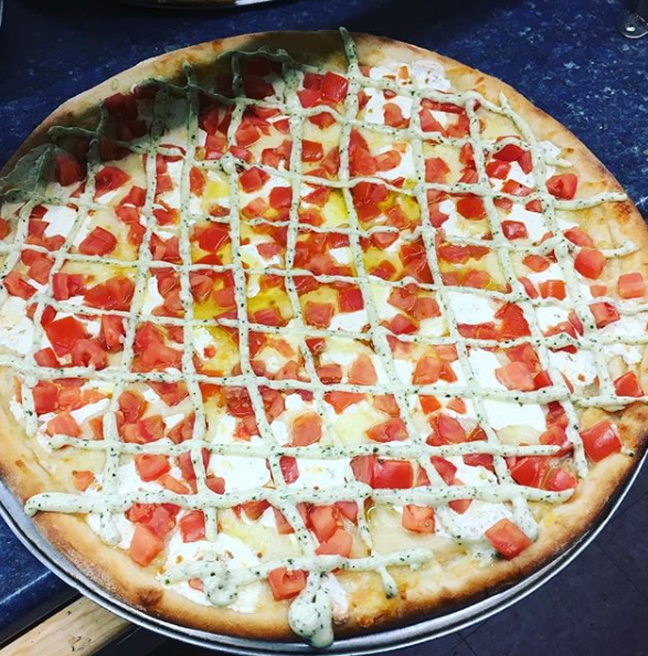 a pizza pie with fresh tomatoes and sauce drizzled on in a lattice
