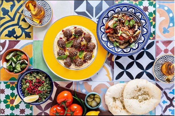 Middle Eastern food served on colorful plates and a colorful tablecloth