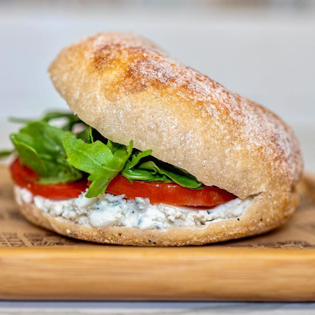cheese, tomato and arugula on a sandwich