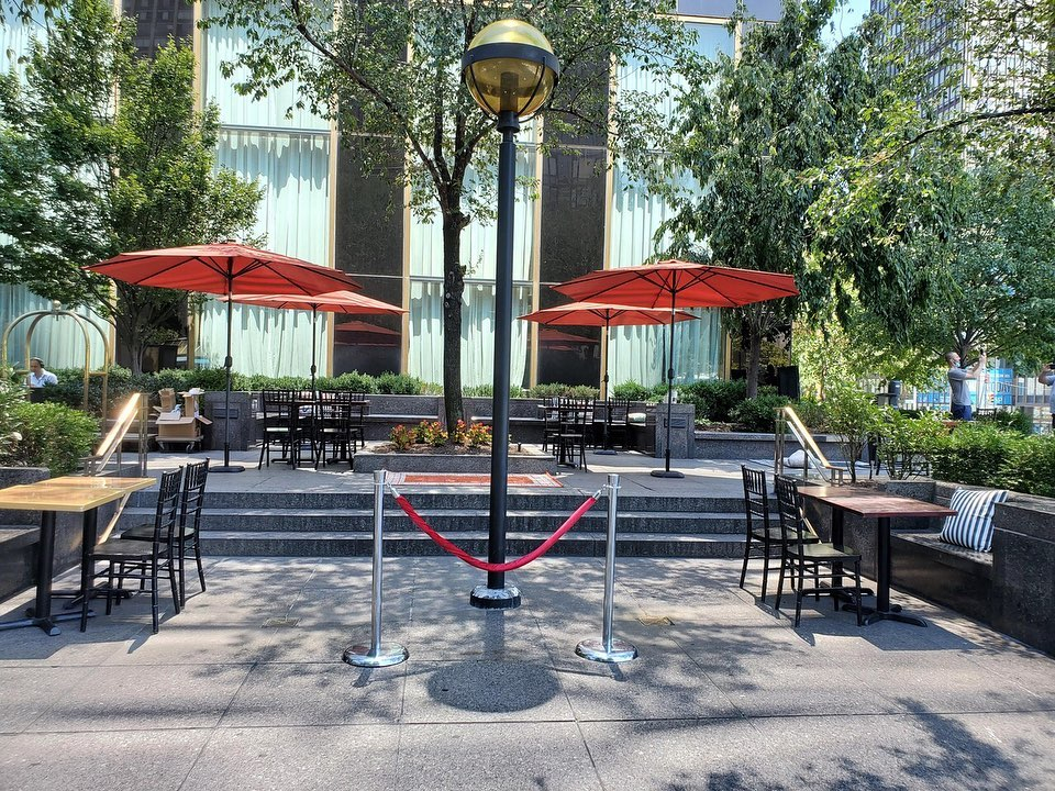 an outdoors seating area with red umbrellas throughout, all surrounded by trees