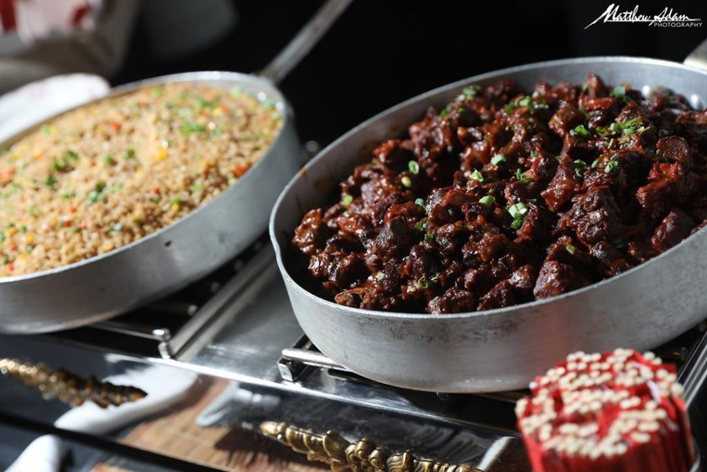 Meat and rice each in a serving dish at a catered event