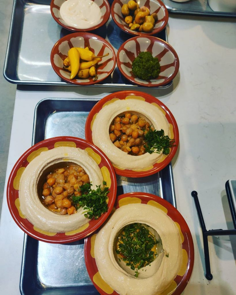 3 plates of hummus and 4 bowls of sides