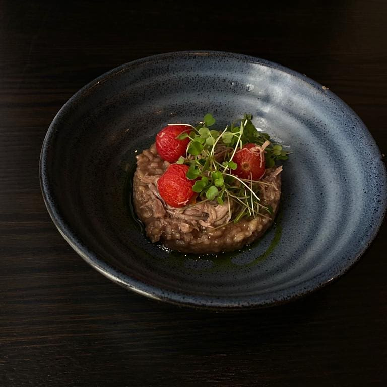 risotto topped with tomatoes and microgreens