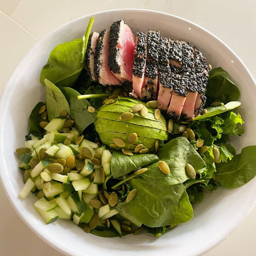 A salad on a bed of greens with apple, pumpkin seeds, avocado and seared tuna
