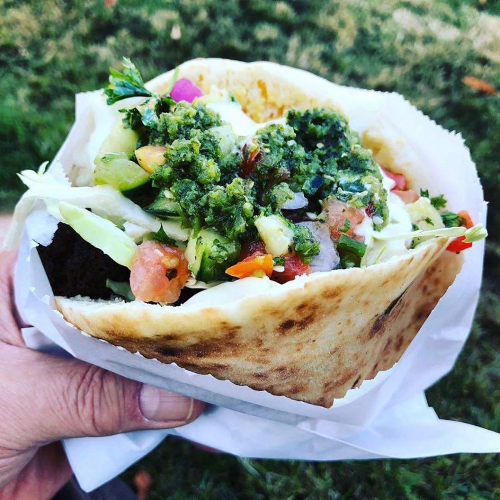 a hand holding a pita filled with falafel and salads