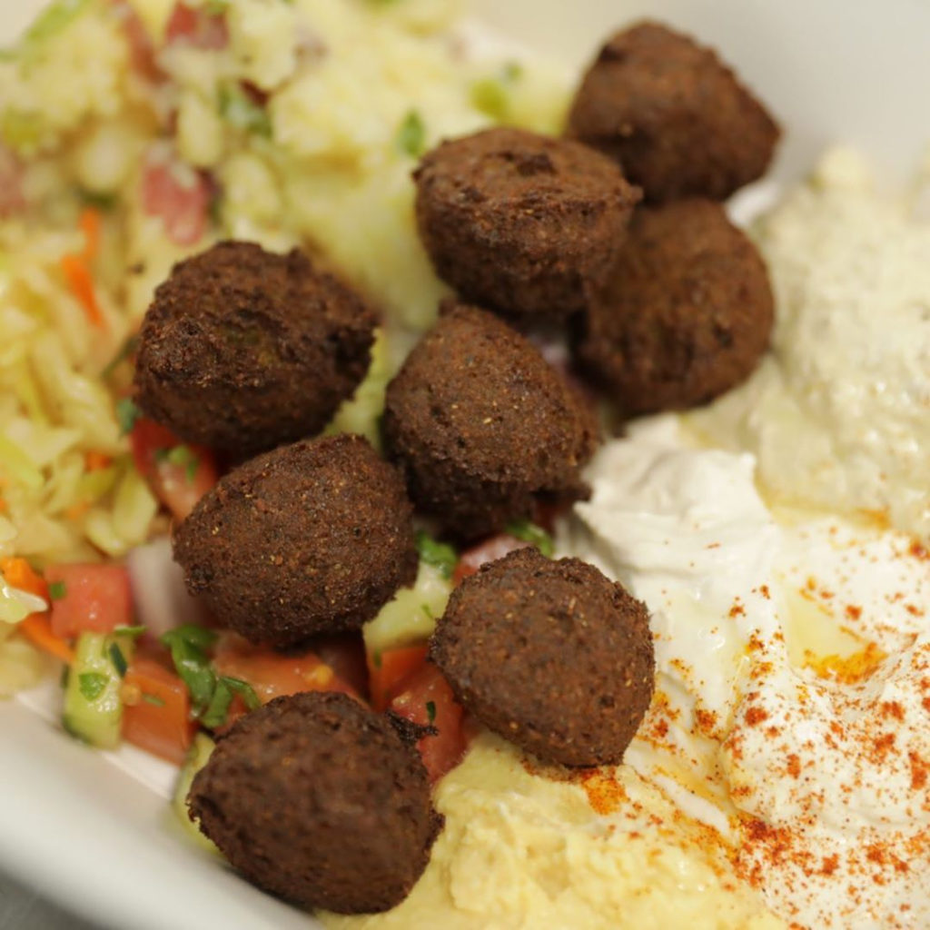 falafel on a plate of hummus and salad