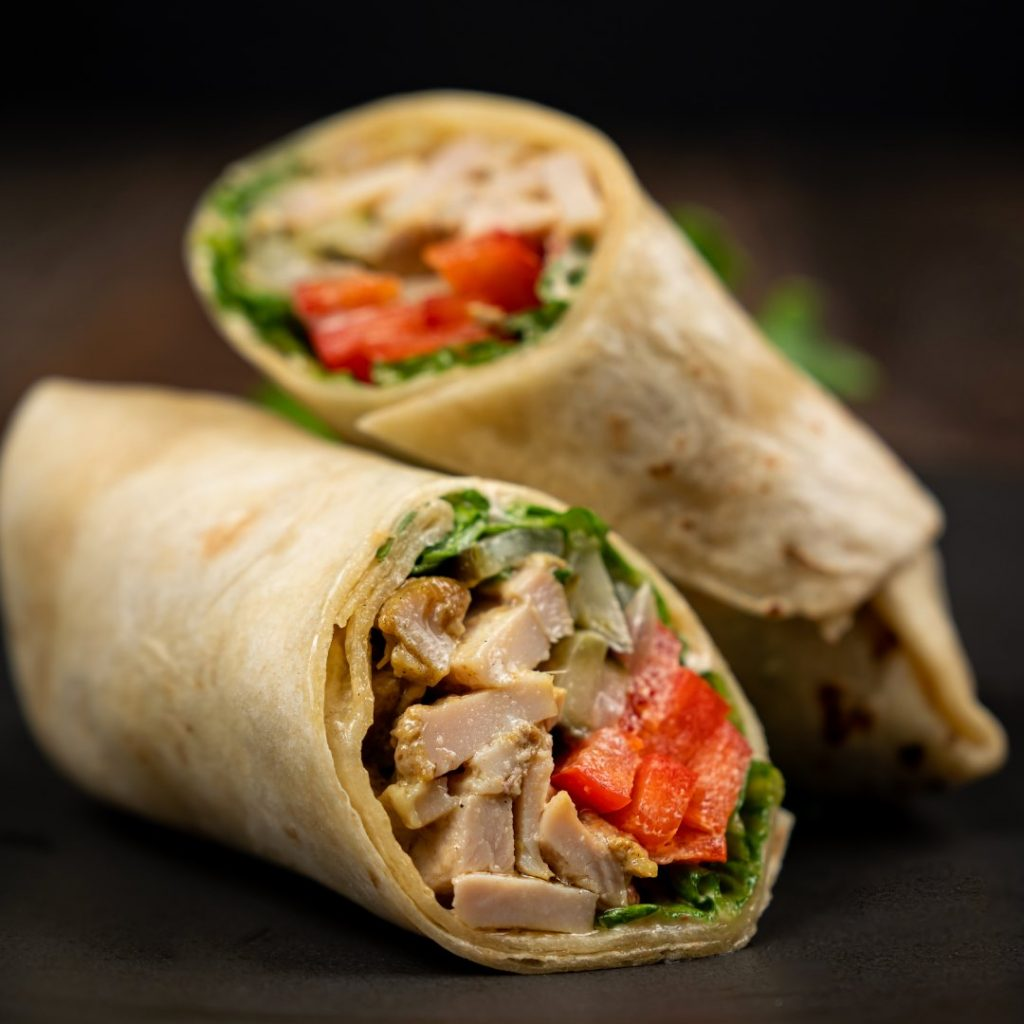 two halves of a chicken wrap, one leaning against the other