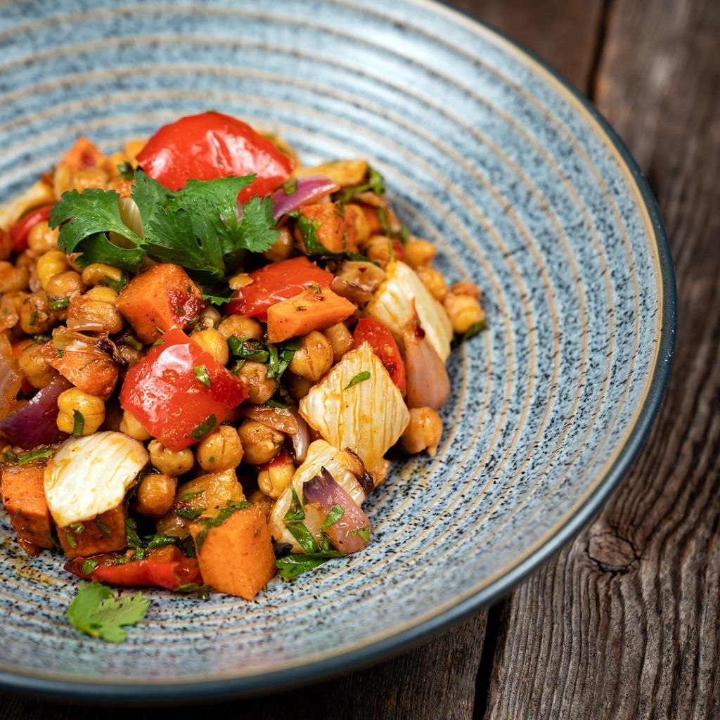 a spiced chickpea and roasted vegetable salad with fresh herbs, served in blue bowl