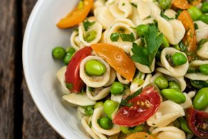 a bowl of pasta with fresh vegetables