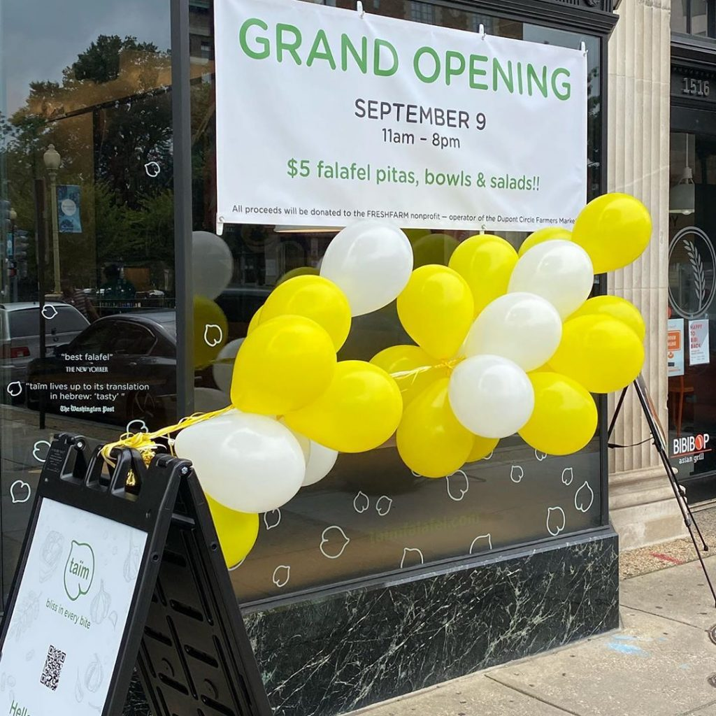 A Grand Opening sign on a store window, with yellow and white balloons