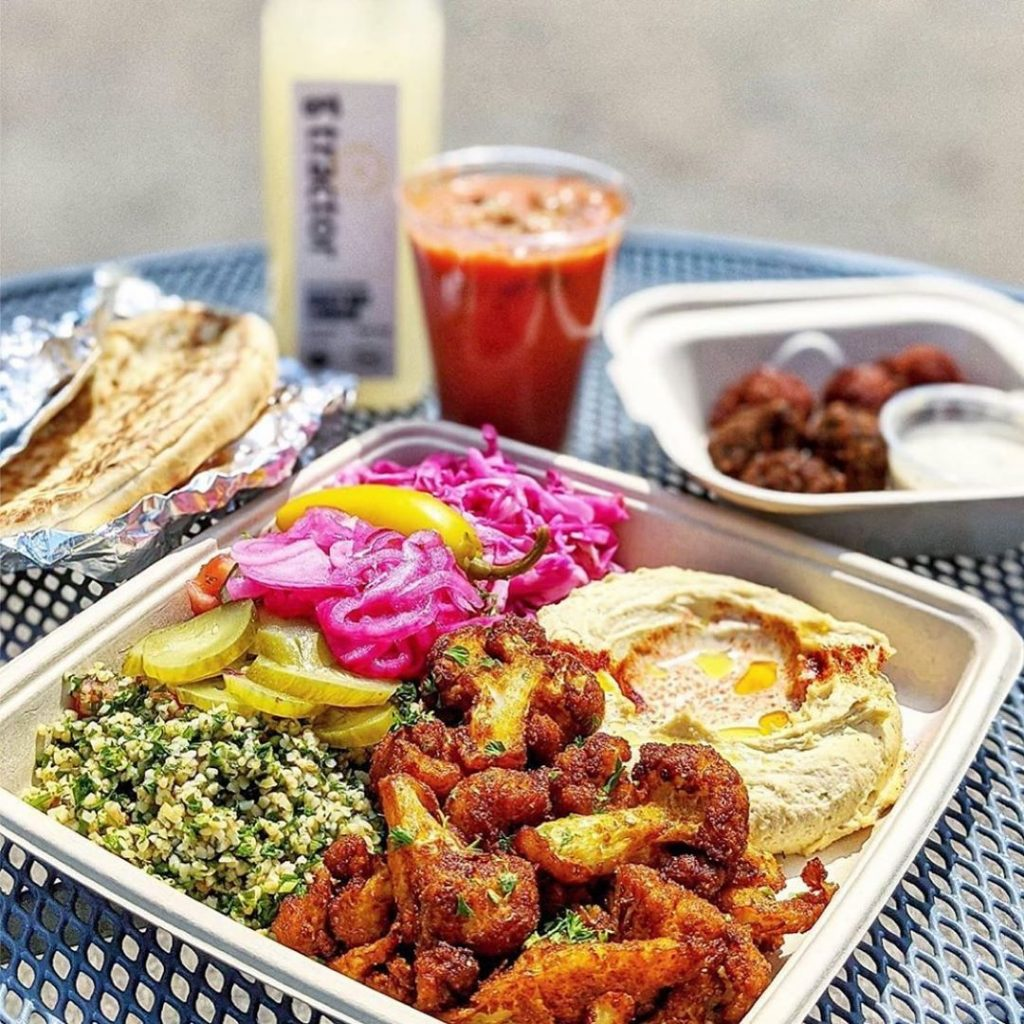 a table with a mixed plate of food, a drink and pita