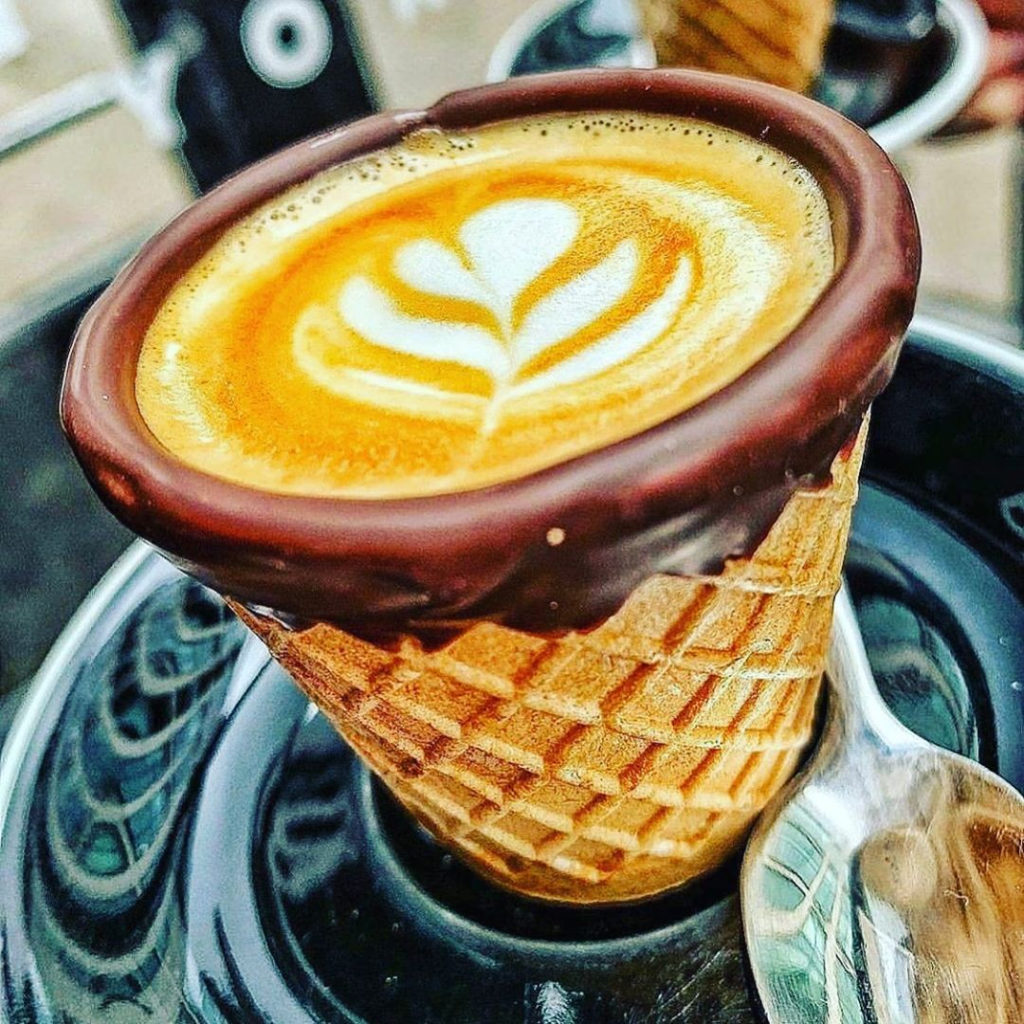 A waffle cone cup with a chocolate rim and filled with coffee