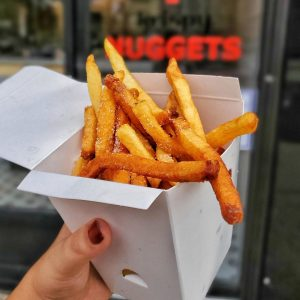 a hand holding a box of fries