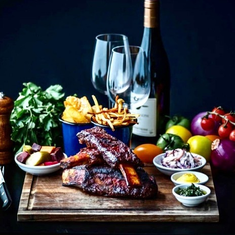 a fancy table with wine, ribs and side dishes on a wooden cutting board