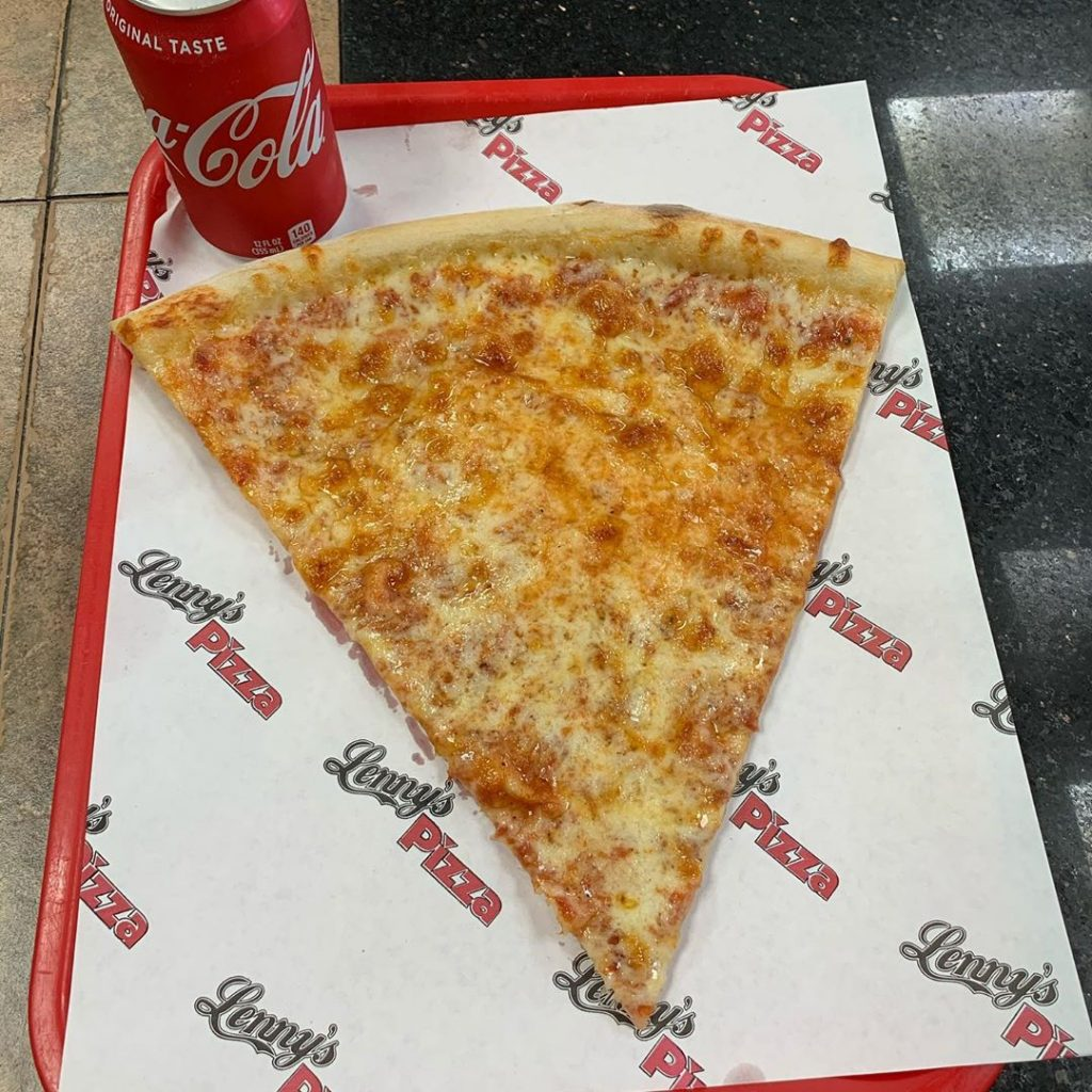 a plain pizza slice and a coca cola on a tray