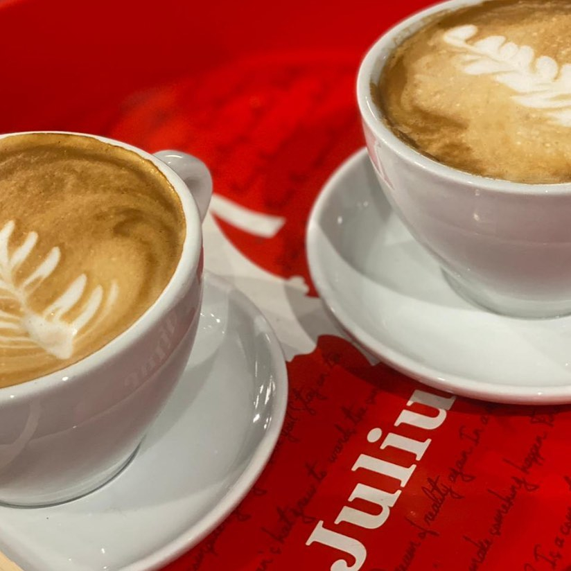 two lattes on white saucers on a red tablecloth
