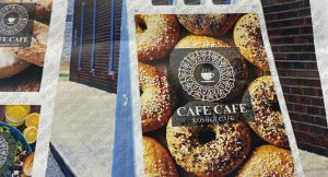 A sign for Cafe Cafe with the name on a background of bagels