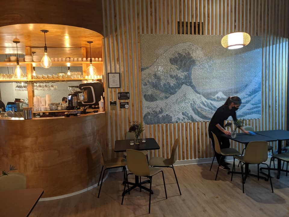 the interior of a restaurant with a wave painting on the wall