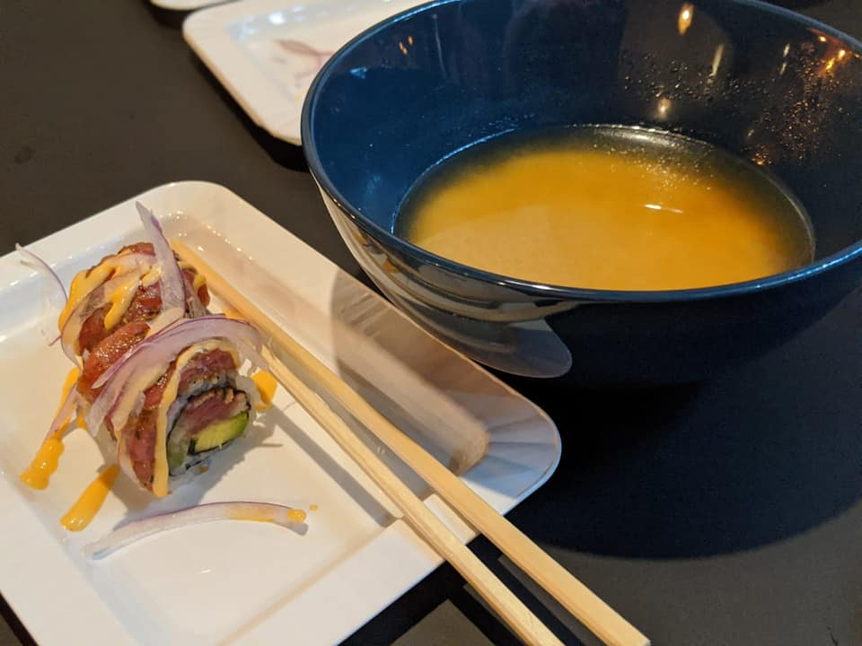 two pieces of sushi on white plate with chopsticks, and soup in a blue bowl