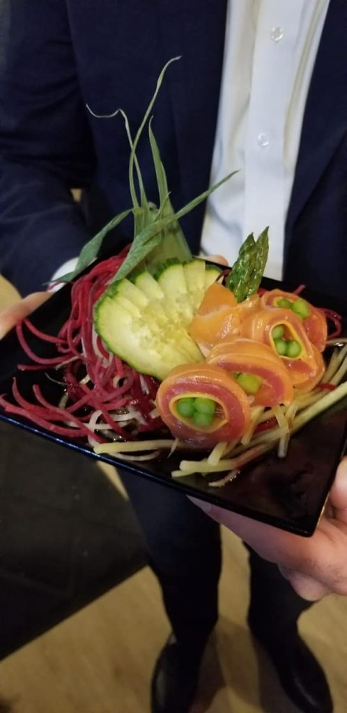a hand holding a plate of colorful sushi