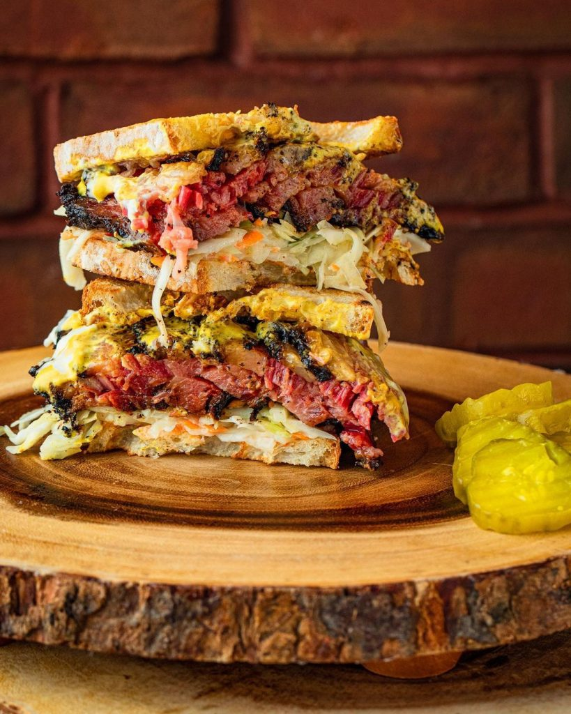 two halves of a stuffed pastrami sandwich stacked on top of each other