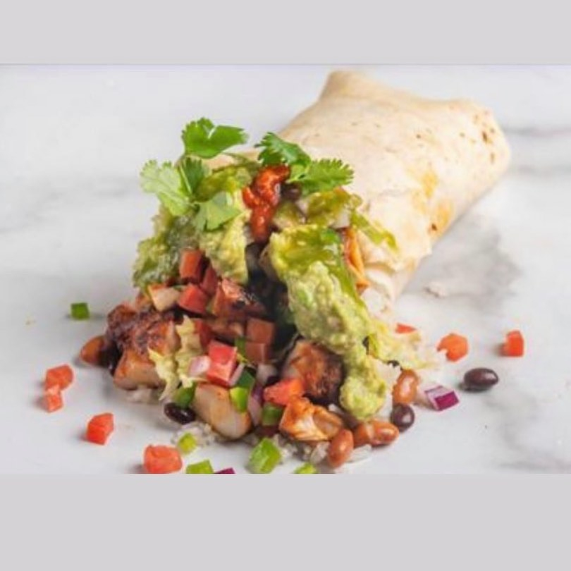 a burrito with the fillings spilling out