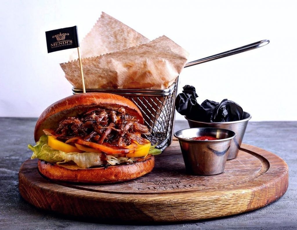 a burger and fries on a wooden circle tray with sauces