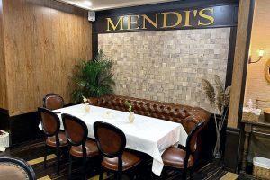 the word Mendi's on a wall above a table in a restaurant