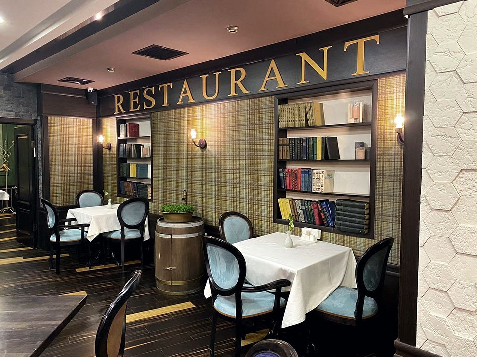 the word restaurant on the wall above tables for three