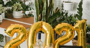 gold 2021 balloons with a happy new year letter board and gold party hats