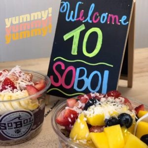 two acai bowls in front of a welcome sign