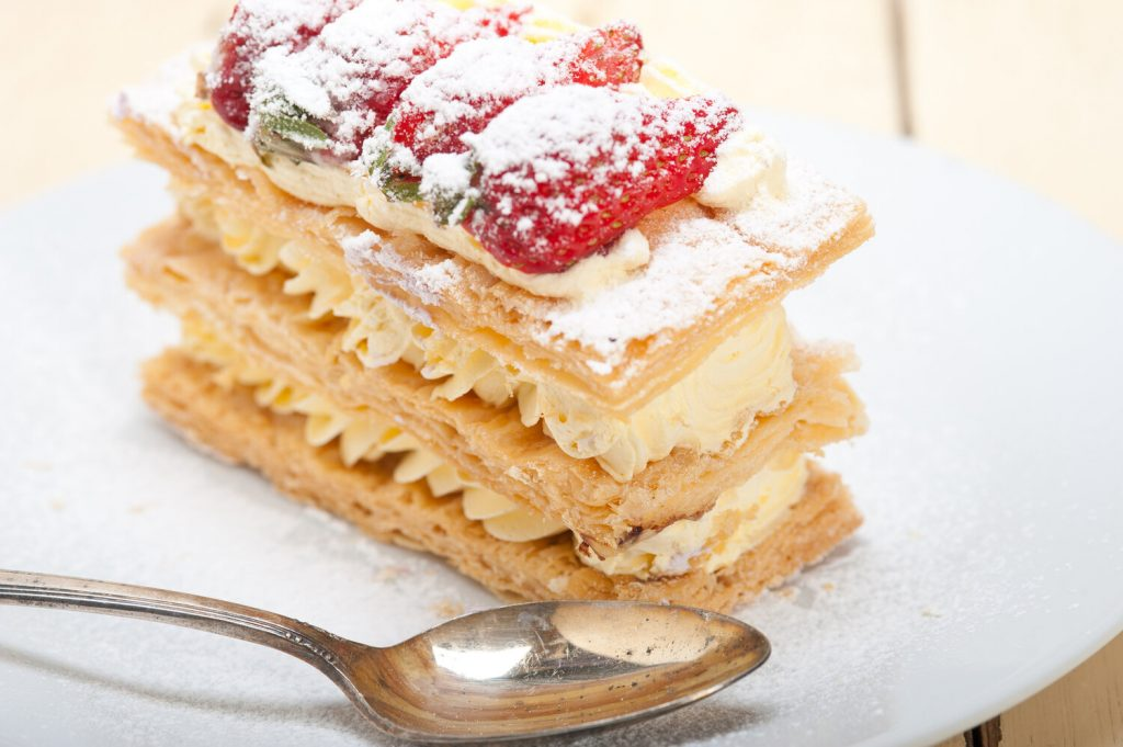 napoleon pastry topped with sugar and strawberries