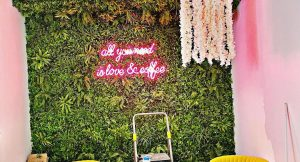 a green grassy wall with pink writing, and yellow chairs and a white table in the foreground