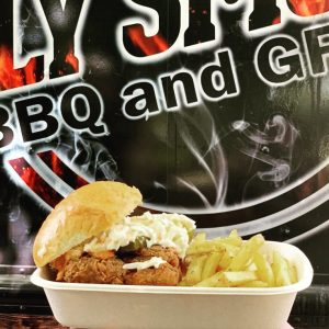 a fried chicken in a disposable container, held up against the holy smokes bbq and grill food truck
