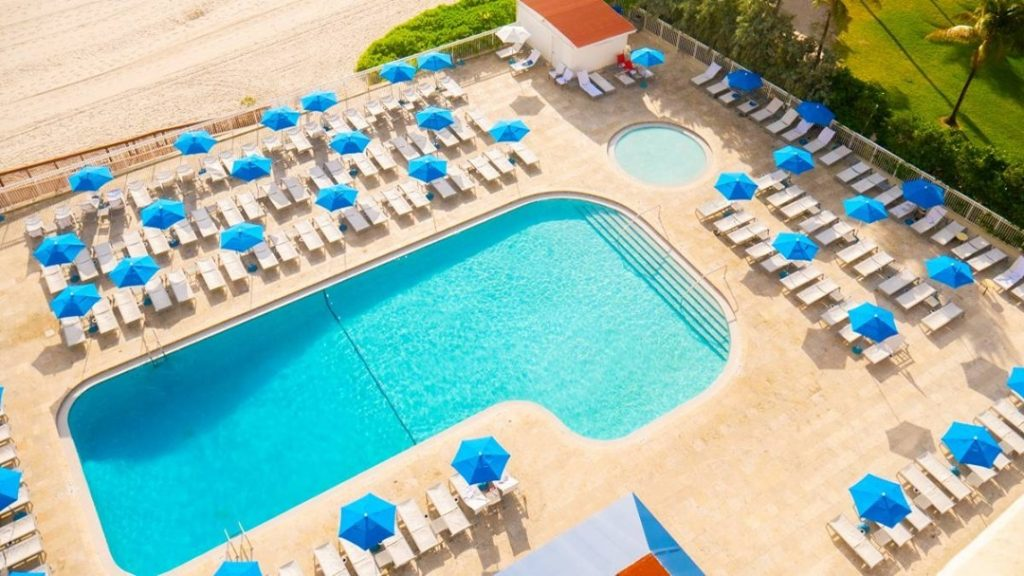 an aerial view of a pool, lounge chairs and umbrellas