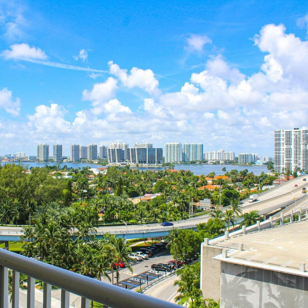 a view of Miami beach buildings past green trees and a highway