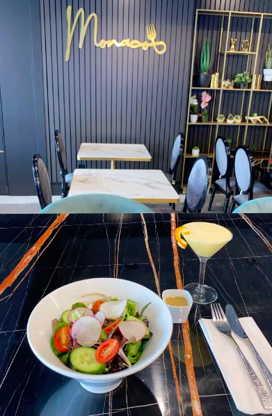 a salad and cocktail on a black marble table in front of a wall with the Monaco logo