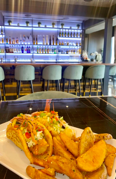 two tacos and fries on a black marble table in front of a bar