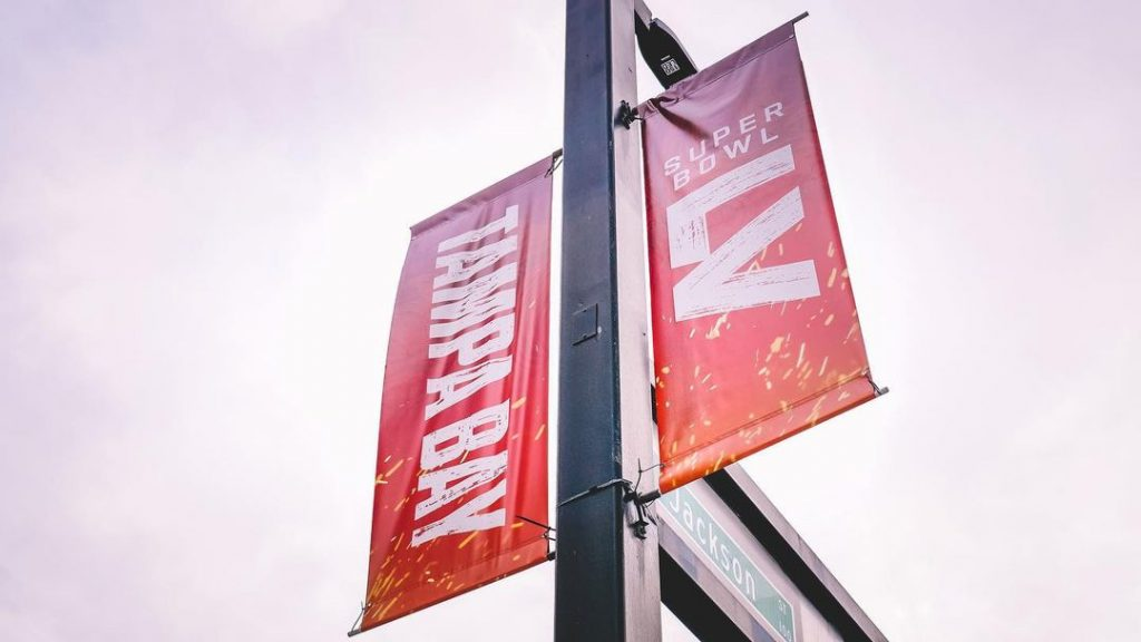 looking up at a sign for Superbowl LV hanging from a light pole in Tampa, Florida