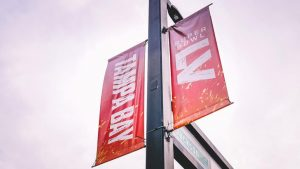 looking up at two signs hanging from a telephone pole. advertising the superbowl