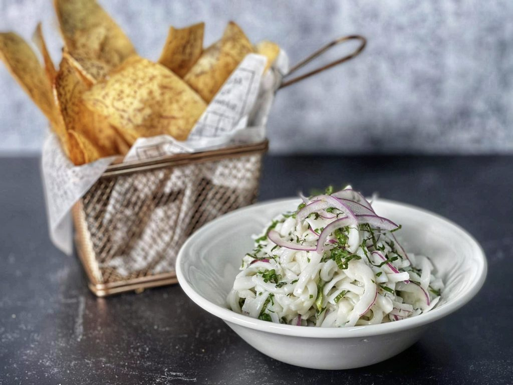 vegan coconut ceviche in a white bowl, with a wire bowl of chips on the side