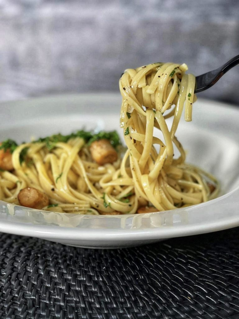 a fork lifting pasta from a white bowl