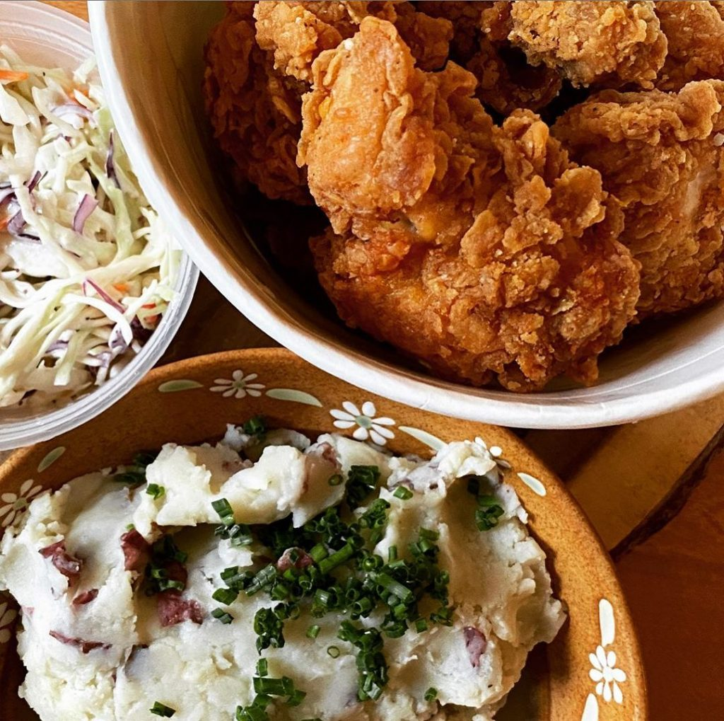 an aerial view of fried chicken, mashed potatoes, and coleslaw on separate plates