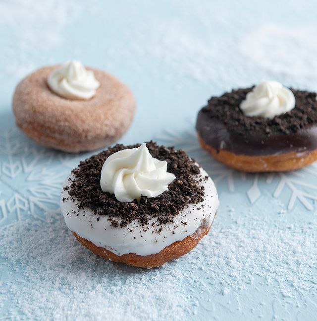 three cookies and cream donuts on a light blue table