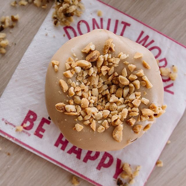 a donut with peanut butter icing and peanut pieces atop a a white napkin with pink writing