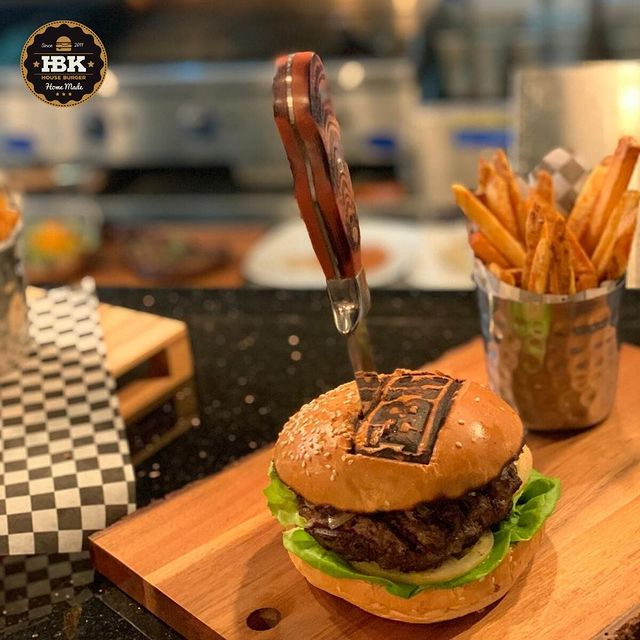 a burger with a steak knife in it, and fries in.a metal cup, all atop a wooden serving board