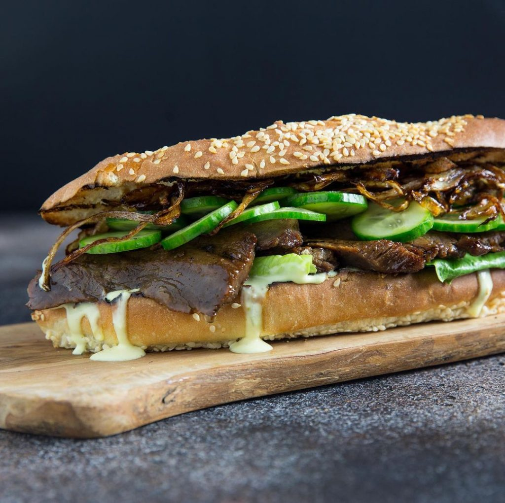 a steak sandwich on a sesame seed baguette