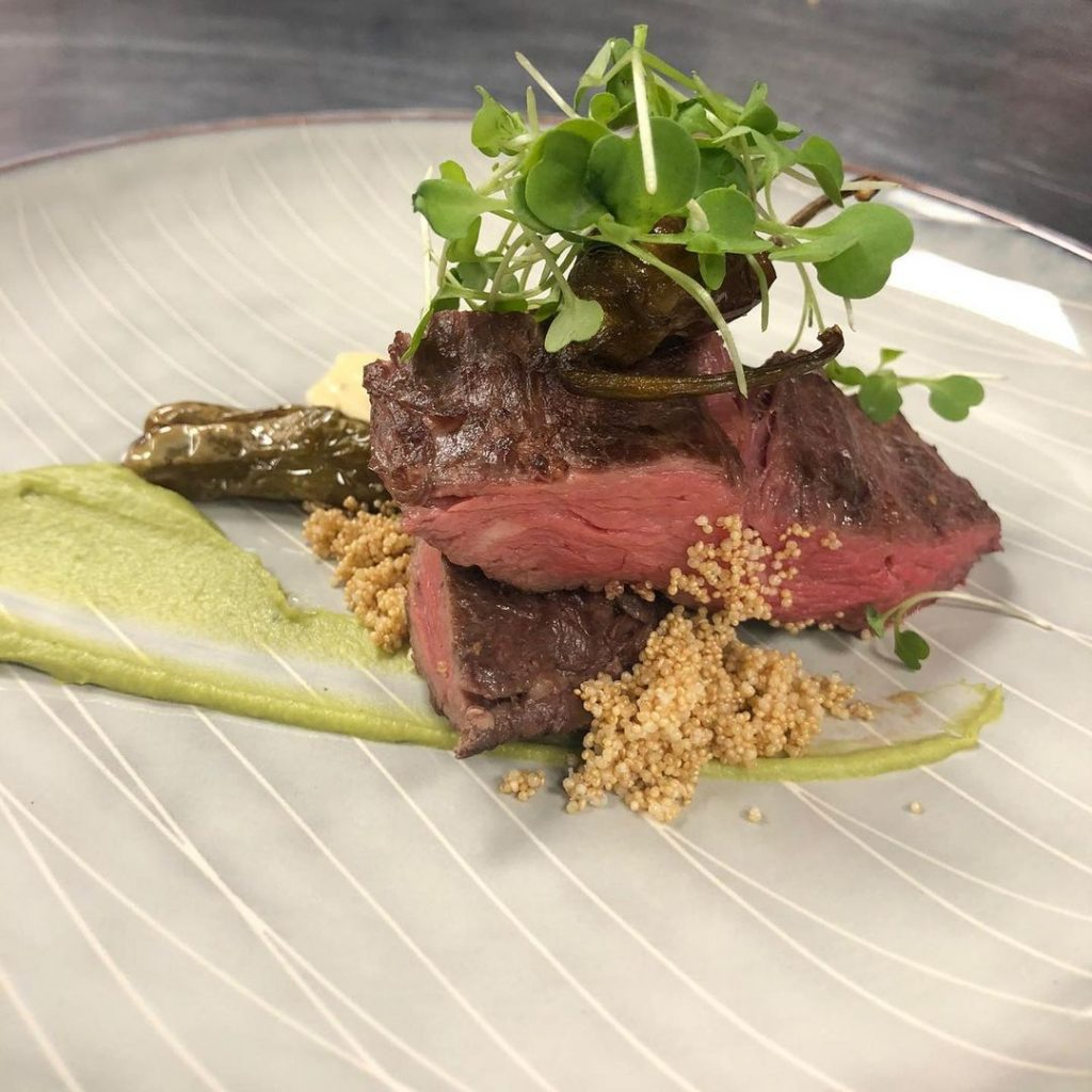 sliced steak on a green sauce topped with microgreens, all on a white plate