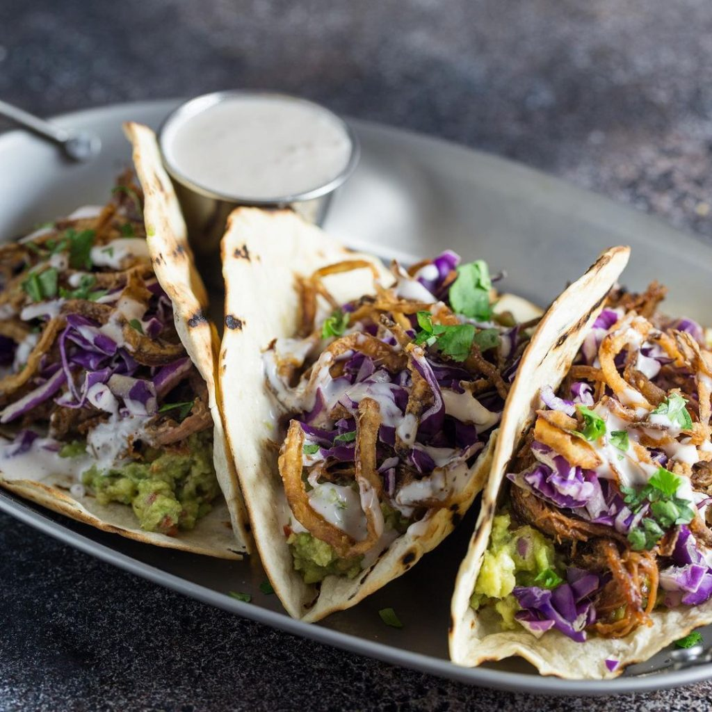 three pulled beef tacos and a white dressing